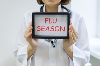 Flu season text in the hands of a female doctor